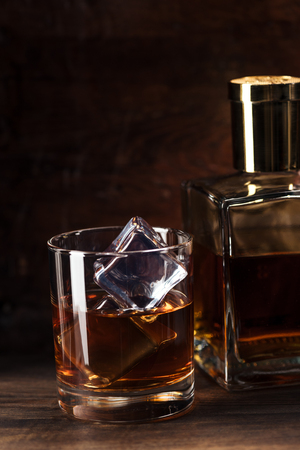 close-up view of glass of cognac with ice cubes and bottle on wooden table 写真素材