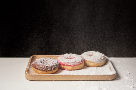 delicious donuts with sifting sugar powder on wooden cutting board