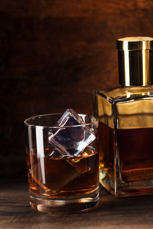 close-up view of glass of brandy with ice cubes and bottle on wooden table