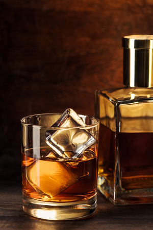 close-up view of glass of whisky with ice cubes and bottle on wooden table Reklamní fotografie - 116407712