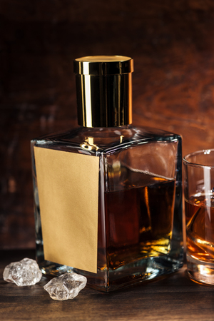 close-up view of whiskey bottle with blank label, ice cubes and glass on wooden table Standard-Bild - 116407716