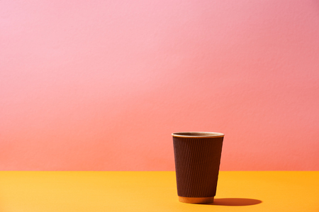 paper coffee cup on yellow surface and pink background