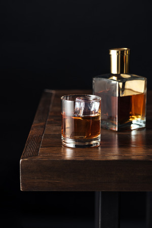 close-up view of glass and bottle of whisky on dark wooden table isolated on black