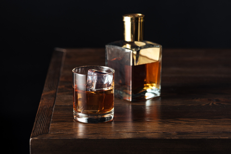 glass and bottle of whisky on dark wooden table isolated on black