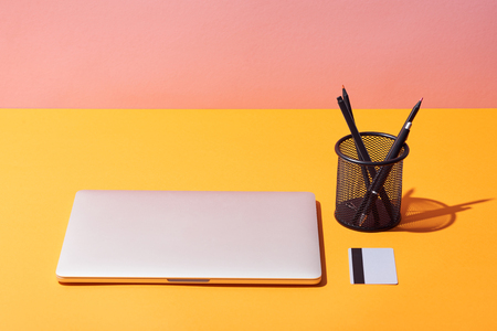 pencil holder near laptop and credit card on yellow surface and pink background