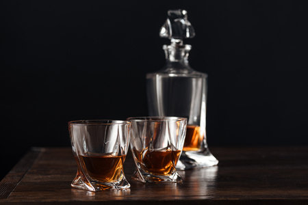 close-up view of glasses and bottle of whisky on dark wooden table isolated on black