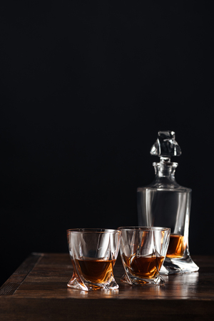 glasses and bottle of whisky on dark wooden table isolated on black 写真素材
