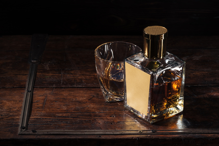 bottle with blank label and glass of whiskey on brown wooden table 写真素材
