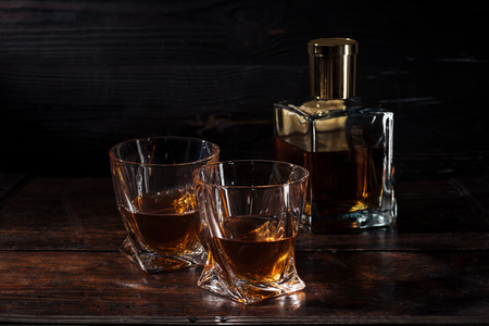 bottle and glasses of whisky on brown wooden table 写真素材
