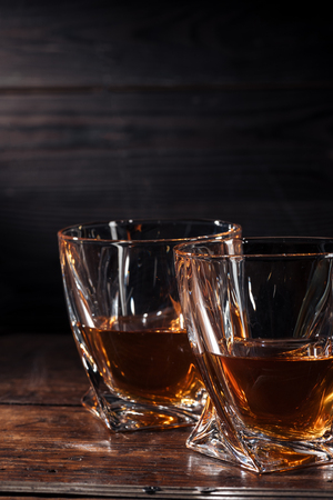 close-up view of two glasses of whisky on dark wooden table