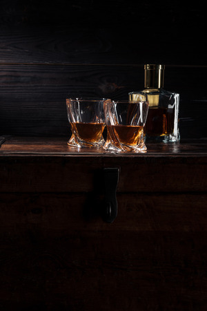 bottle and glasses of whiskey on vintage wooden table