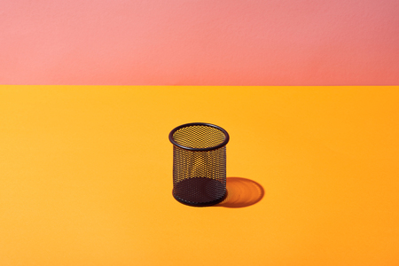 empty pencil holder on yellow surface and pink background Banco de Imagens