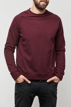 partial view of man with hands in pockets in burgundy sweatshirt with copy space isolated on grey Stock Photo