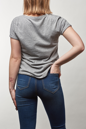 back view of young woman in casual grey t-shirt with copy space isolated on white 免版税图像