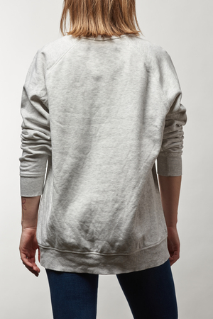 back view of young woman in casual grey hoodie with copy space isolated on white