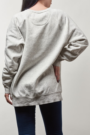 back view of young woman in grey hoodie with copy space isolated on white