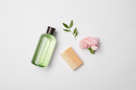 Top view of different cosmetic bottles, soap, tea plant branch and carnation flower on white background