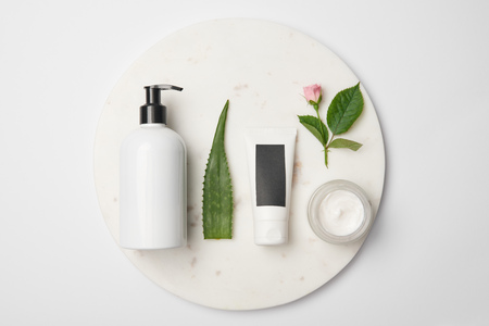 Top view of different cosmetic containers, aloe vera leaf and rose flower on white round surface