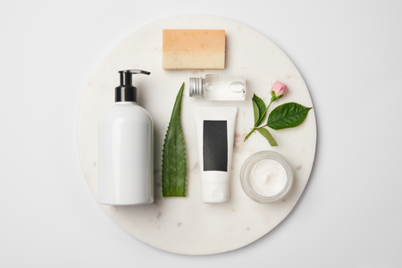 Top view of different cosmetic containers, soap, aloe vera leaf and rose flower on white round surface