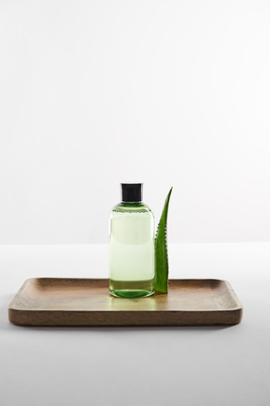 transparent cosmetic bottle and aloe vera leaf on wooden tray on white surface
