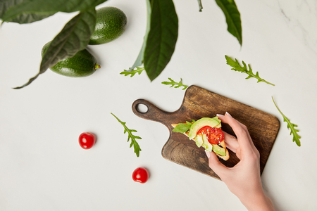 top view of womans hand holding toast, wooden cutting board, avocados and cherry tomatoes under green plant on marble surface