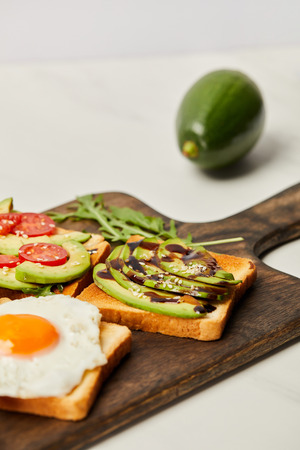 selective focus of wooden cutting board with toasts, scrambled egg, cherry tomatoes and avocado on grey background