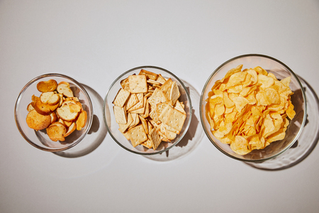 top view of salty snacks in glass bowl on white background