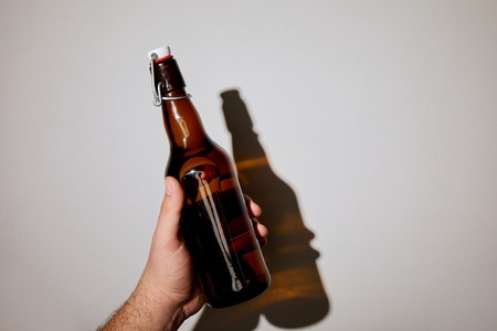 cropped view of man holding bottle with beer on white background Stock Photo