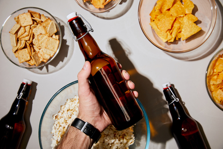selective focus of man holding bottle with beer near snacks in bowls on white background Stock Photo - 116407258