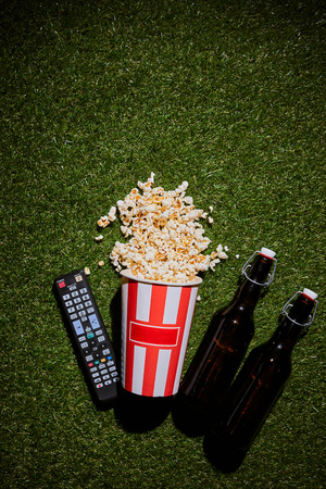 top view of  bottles of beer near popcorn cup and remote control lying on grass