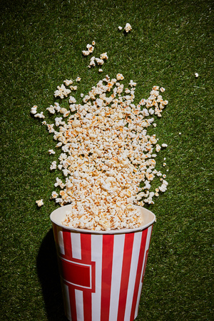 top view of tasty popcorn lying on grass near popcorn cup 스톡 콘텐츠