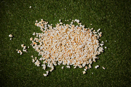 top view of tasty popcorn lying on green grass 스톡 콘텐츠
