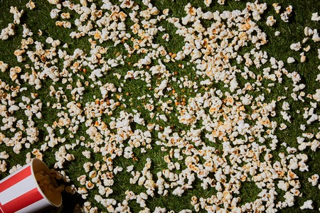 top view of delecious popcorn lying on green grass Stock fotó