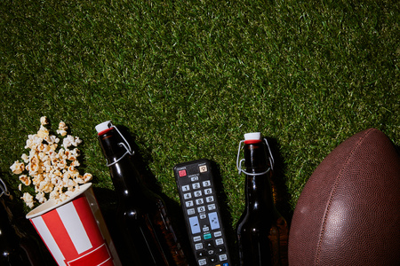 flat lay of brown bottles near popcorn, remote control and ball lying on grass