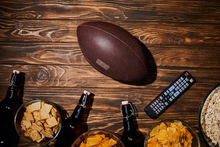 top view of tasty snacks near bottles and ball on wooden table