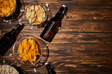 top view of snacks in bowls near brown bottles with beer on wooden table