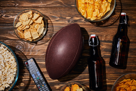 top view of party snacks in bowls near brown bottles with beer and ball on wooden table