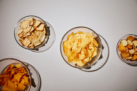 top view of glass bowls with tasty snacks on white background