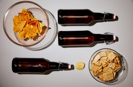 top view of bottles with beer near tasty snacks on white background