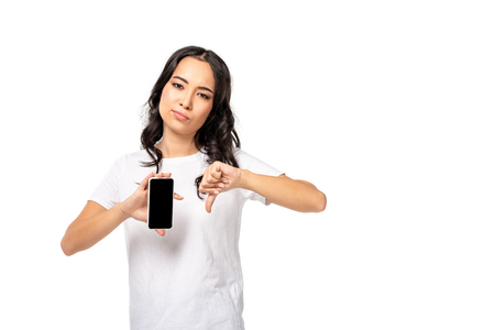 unpleased asian woman holding smartphone with blank screen and showing thumb down isolated on white