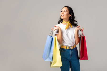 Happy young asian woman holding colorful shopping bags on raised hands isolated on grey