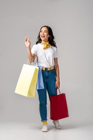 Mujer asiática joven vestida de moda sosteniendo coloridas bolsas de la compra y saludando con la mano levantada en gris