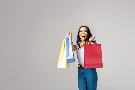 Smiling asian woman holding colorful shopping bags on raised hands and looking at camera isolated on grey Stock Photo