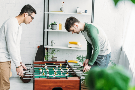 multicultural friends playing table football in spacious living room Stock Photo