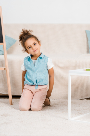 adorable african american child kneeling on carpet and smiling at camera