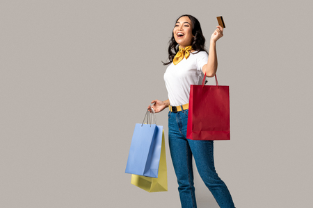 Smiling trendy dressed asian woman carrying colorful shopping bags and holding credit card isolated on grey