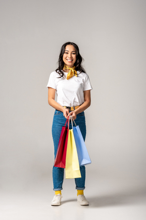 Attractive smiling asian woman holding colorful shopping bags on grey