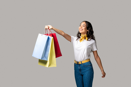 Happy smiling asian girl holding colorful shopping bags in one stretched hand isolated on grey