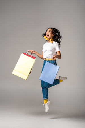 Beautiful young asian woman jumping up with happy smile while holding colorful shopping bags on grey