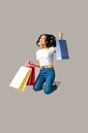 Excited asian woman holding colorful shopping bags and happily jumping with one raised hand isolated on grey Banque d'images - 117775023